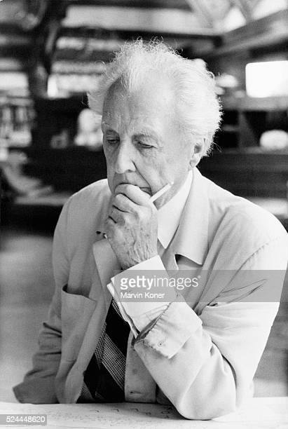 American architect Frank Lloyd Wright contemplates a drawing at the Hillside Drafting Studio on the Taliesin Estate | Location Spring Green Wisconsin...