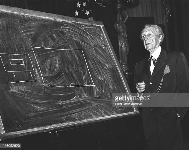 American architect Frank Lloyd Wright stands beside a diagram drawn on a chalkboard New York New York 1952