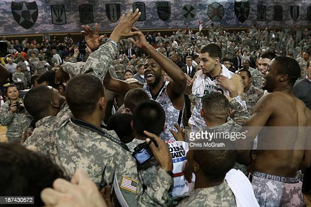 American Armed Forces personnel celebrate victory with Mike Moser of the Oregon Ducks after they defeated the Georgetown Hoyas during the Armed...