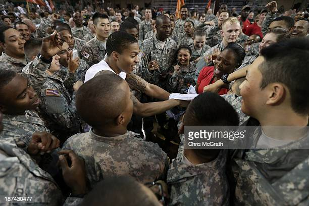American Armed Forces personnel pull the uniform off Joseph Young of the Oregon Ducks after they defeated the Georgetown Hoyas during the Armed...