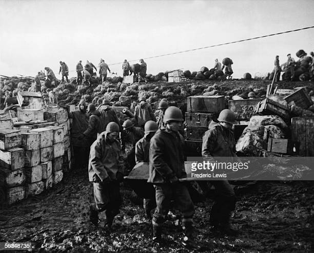 American Army and Navy men tredge through thick gumbo mud carrying and unloading supplies and ammunition to the base on Amchitka in the Aleutian...