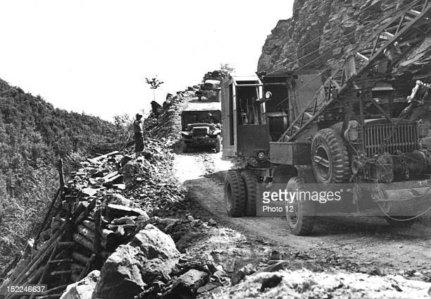 American Army equipment rolls over a road built by 5th Allied Army engineers after retreating Germans had blasted this mountain bend near Firenze...