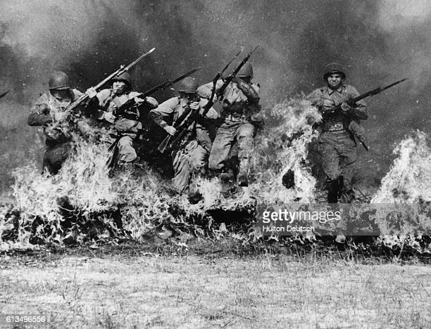 American army ranger troops run through a wall of fire as land mines explode behind them during training manoeuvres at Camp Hocker