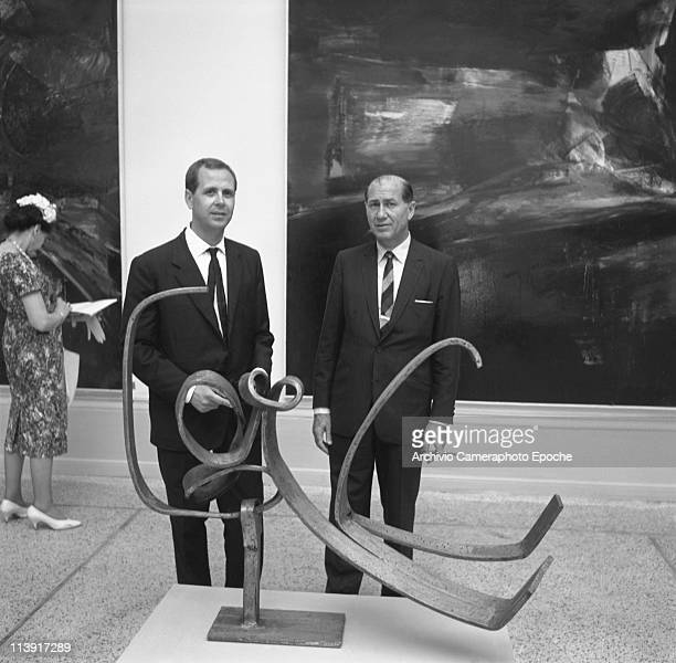 American art promoter David E Bright wearing a suit and a striped tie and smoking a cigar standing with a man behind a sculpture during the art...