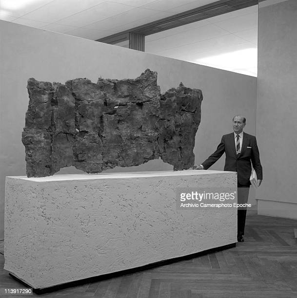American art promoter David E Bright wearing a suit and a striped tie standing next to a sculpture during the exposition of the Art Biennale in...
