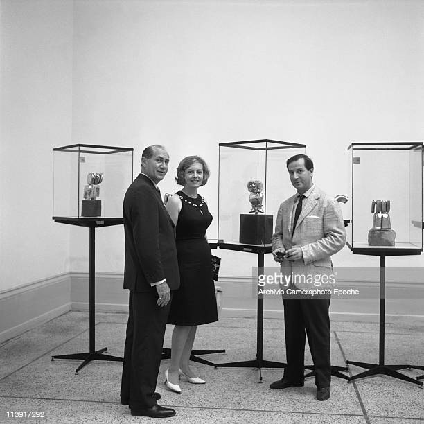 American art promoter David E Bright with a man and a woman standing next to some sculpture during the Art Biennale Venice 1964
