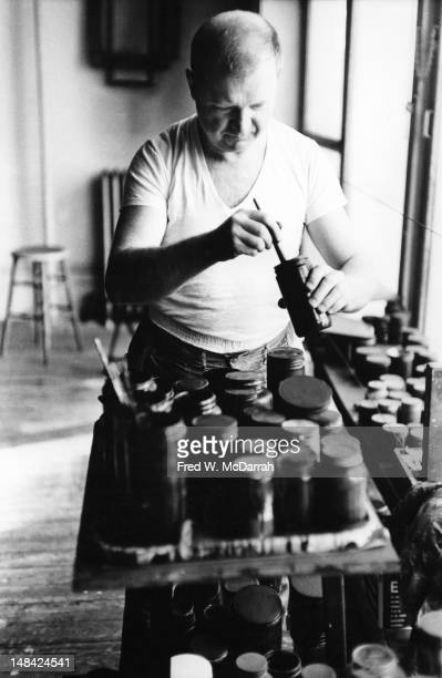 American artist Ad Reinhardt stirs paint in the loft studio New York New York March 1 1962