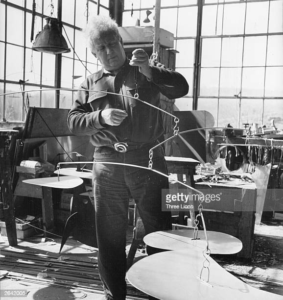 American artist Alexander Calder at work in his Connecticut studio where he turns sheets of iron into mobiles