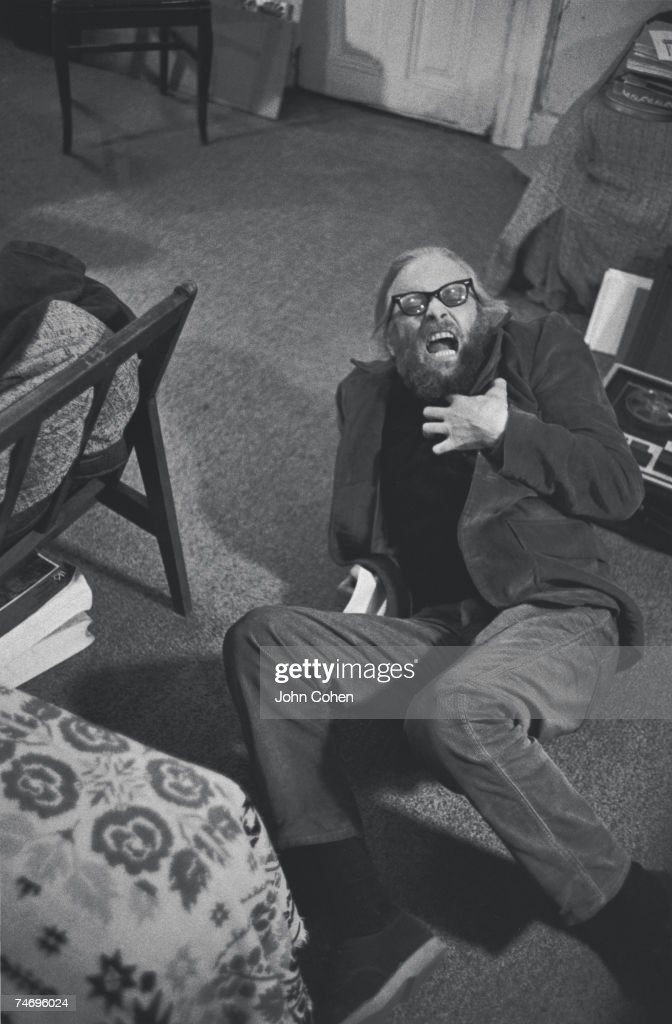 American artist and archivist Harry Everett Smith (1923 - 1991) adopts a posture of mock pain as he writhes on the floor of a room at the Chelsea Hotel and clutches at his chest, New York, New York, 1969.