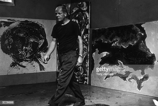 American artist and author Jackson Pollock in front of three of his paintings which are in progress at his studio East Hampton New York