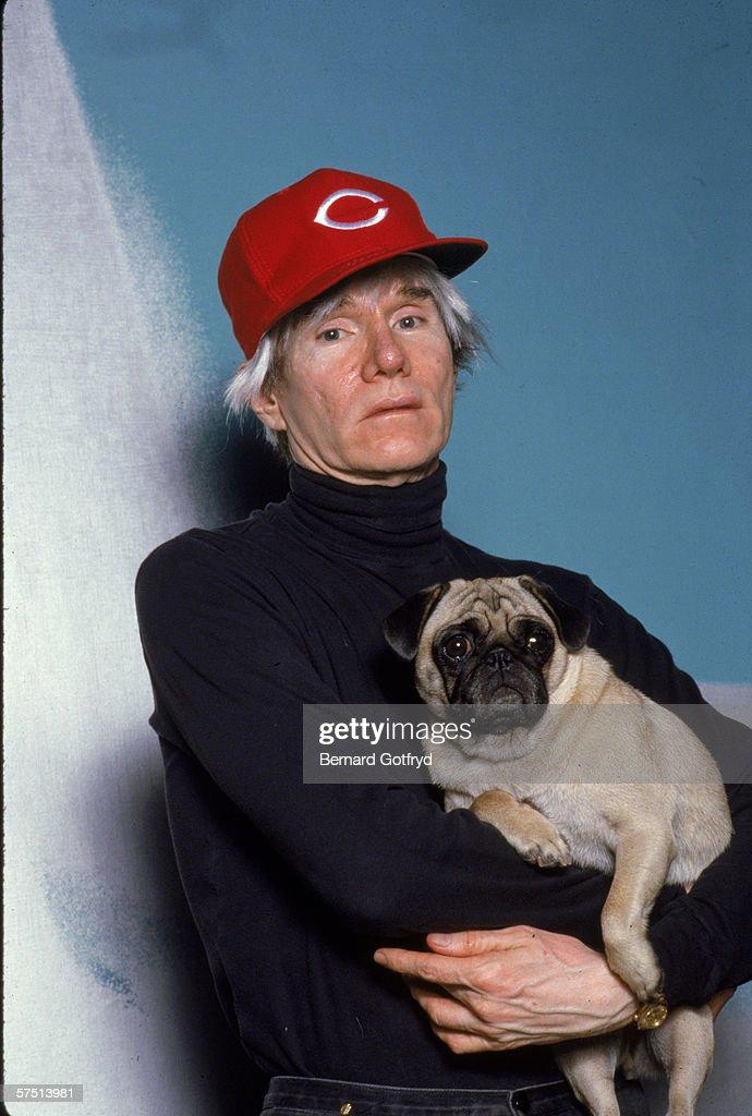 American artist Andy Warhol (1928 - 1987), in a Cincinnatti Reds baseball cap, holds a pug, 1980s.