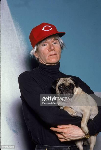 American artist Andy Warhol in a Cincinnatti Reds baseball cap holds a pug 1980s