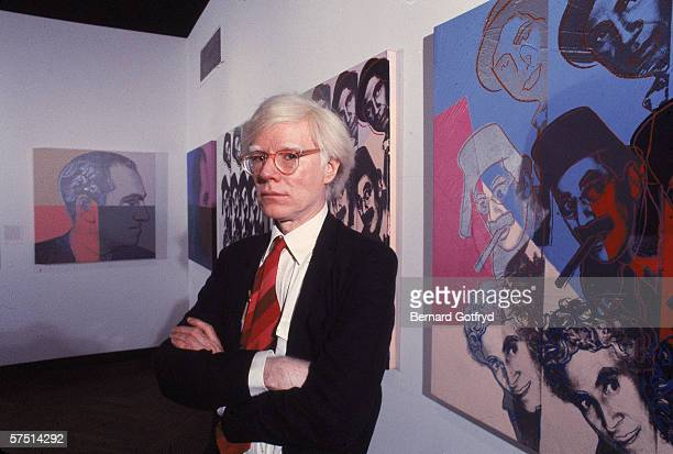 American artist Andy Warhol poses in front of his screenprints of the Marx Brothers and George Gershwin, part of his series 'Ten Portraits of Jews of...