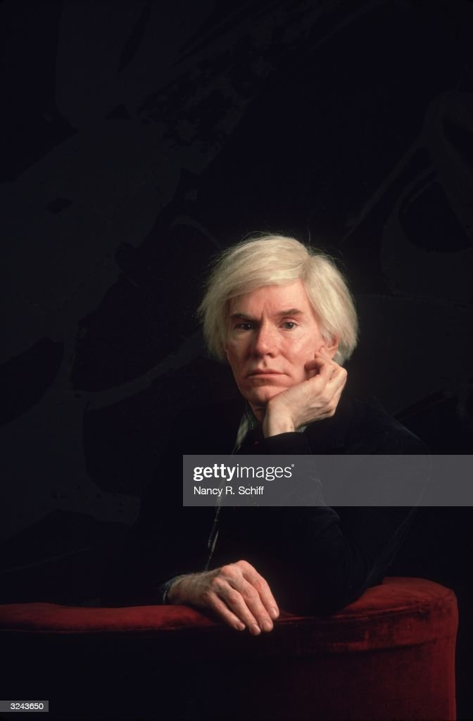 American artist Andy Warhol (1928 - 1987) sitting in a red velvet chair with his chin propped on his hand, in an all-black setting.