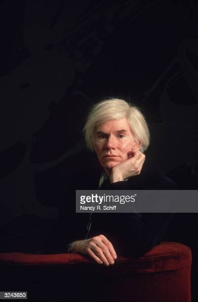 American artist Andy Warhol sitting in a red velvet chair with his chin propped on his hand in an allblack setting