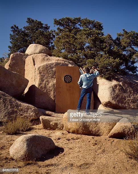 American artist Edward Ruscha with a dartboard at his desert house, California, June 1985 .