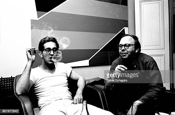 American artist Frank Stella blows smoke rings from a cigar as he sits with curator and historian Henry Geldzahler New York New York 1965