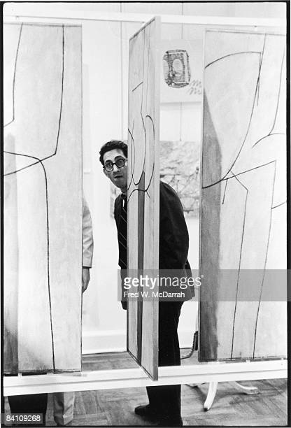 American artist Frank Stella peers from behind a painting mounted on a swivel frame at an unidentified gallery New York New York late 1950s or early...