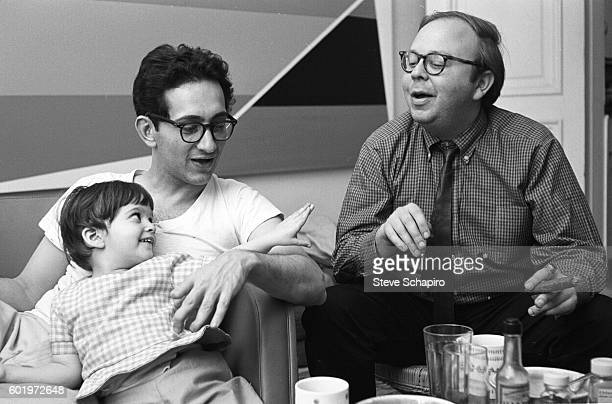 American artist Frank Stella sits with his son Michael and curator and historian Henry Geldzahler New York New York 1965