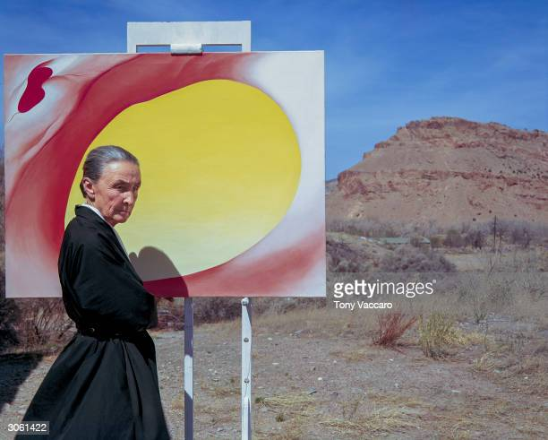 American artist Georgia O'Keeffe poses outdoors beside an easel with a canvas from her series 'Pelvis Series Red With Yellow' Albuquerque New Mexico...