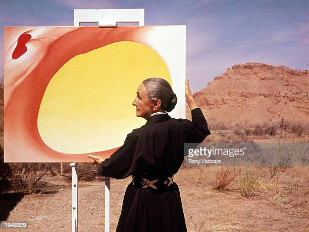 American artist Georgia O'Keeffe stands at an easel outdoors adjusting a canvas from her 'Pelvis Series Red With Yellow' Albuquerque New Mexico 1960