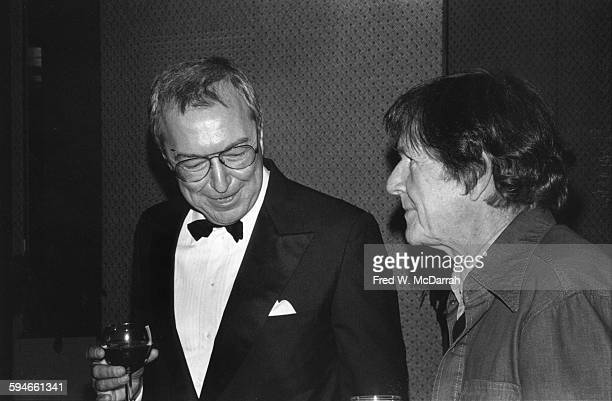 American artist Jasper Johns dressed in a tuxedo holds a wine glass as he talks with composer John Cage at a concert New York New York March 30 1981