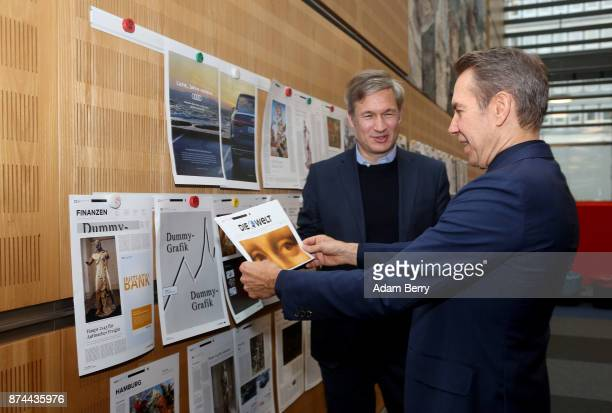 American artist Jeff Koons and Ulf Poschardt editorinchief of the Die Welt newspaper look at mockups of the special edition of the paper that Koons...