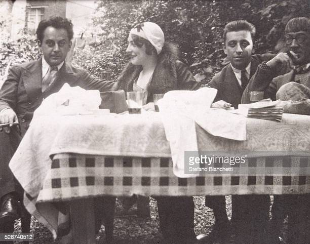 American artist Man Ray Madame Auspach French poet Robert Desnos and French artist Tsugouharu Foujita sit at a table outdoors | Located in...