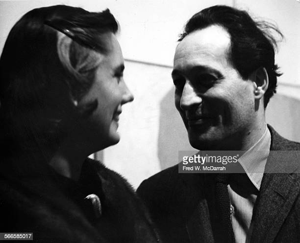 American artist Norman Bluhm speaks with an unidentified woman at an event in the Martha Jackson Gallery New York New York March 24 1959