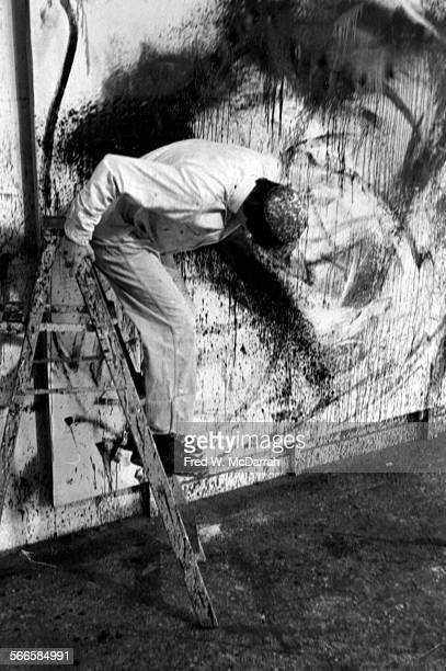 American artist Norman Bluhm works on the oversized canvas of one of his action paintings in his studio New York New York February 22 1961