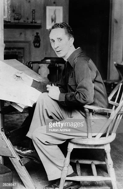 American artist Norman Rockwell looks up while seated at his drawing table, circa 1945.