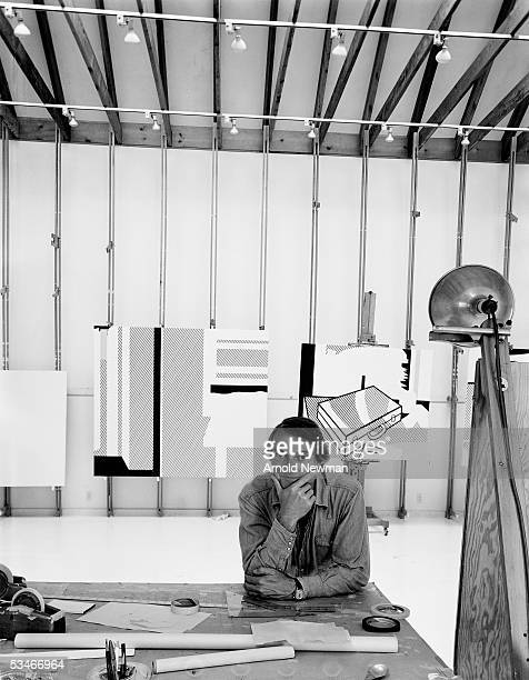 American artist Roy Lichtenstein sits at his work table in his studio Southhampton Long Island New York September 18 1976 Behind him are two of his...