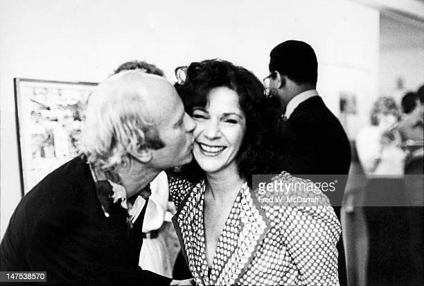 American artist Ruth Kligman smiles as fellow artist James Rosenquist kisses her on the cheek at a party New York New York May 16 1975