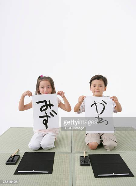 American Asian girl and Japanese boy sitting on tatami, and writing