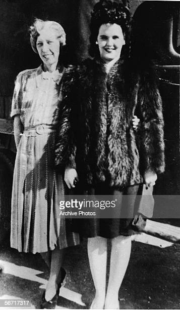 American aspiring actress and murder victim Elizabeth Short known as the 'Black Dahlia' wears a fur coat and stands with her mother Phoebe Mae Short...