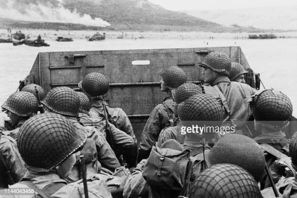 American assault troops in a landing craft huddle behind the shield 06 June 1944 approaching Utah Beach while Allied forces are storming the Normandy...