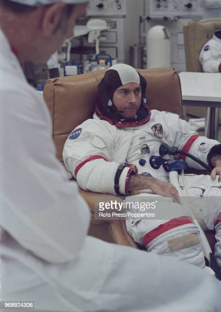 American astronaut and Mission Commander of the Apollo 16 manned mission to the Moon John Young talks with technician Clyde Teague during a spacesuit...
