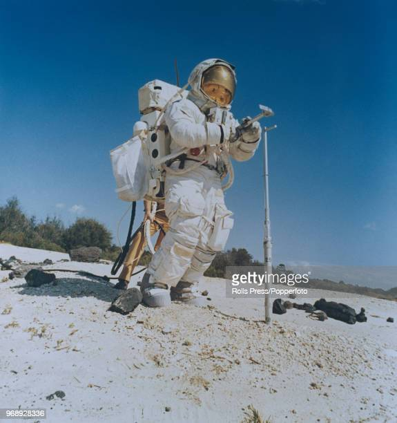 American astronaut and Mission Commander of the Apollo 16 manned mission to the Moon John Young wearing a full space suit carries out a geological...