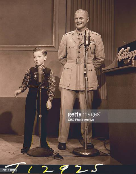 American astronaut and politician Major John Glenn and child actor Eddie Hodges stand at microphones next to a podium with a 'Kelloggs' sign and...