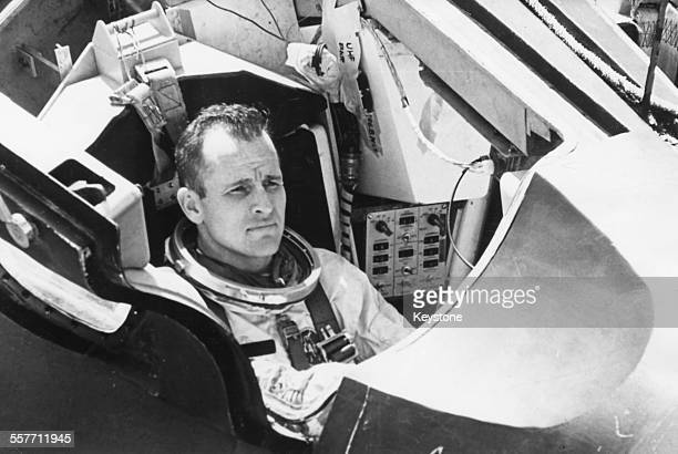 American astronaut Edward H White checking procedures in the spacecraft prior to escape training for the Gemini 4 mission where he will be the first...