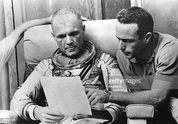 American astronaut Lt Col John Glenn checks over notes with backup pilot Scott Carpenter after a simulated flight prior to the MercuryAtlas 6 mission...