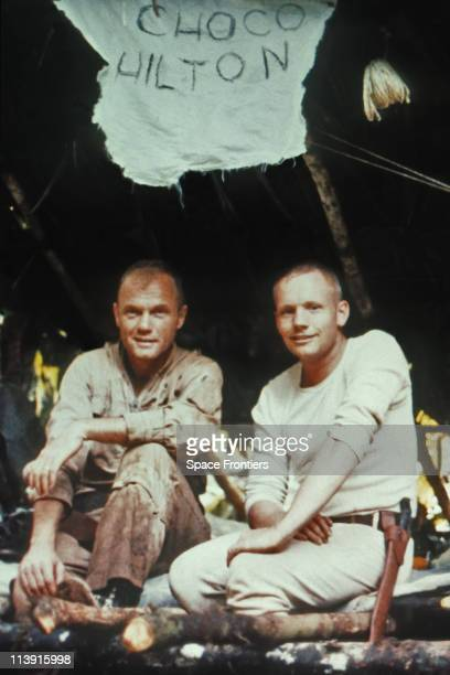 American astronauts John Glenn and Neil Armstrong during survival training in the Darien rainforest of Panama, circa 1963. Above them is a sign...