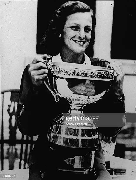 American athlete and golfer Babe Zaharias holds a trophy aloft after winning a tournament 1940s