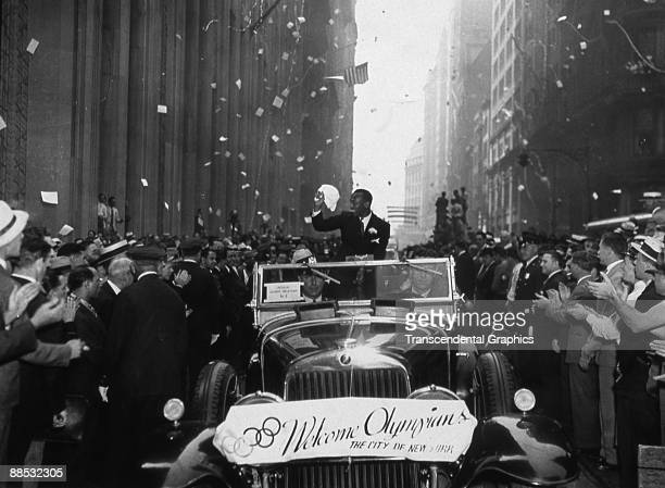 American athlete and Olympic gold medal winner Jesse Owens smiles as he waves at fans who line the streets during a ticker tape parade in honor of...