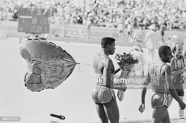 American athlete and sprinter Carl Lewis celebrates with a bouquet of flowers and a large balloon with text 'Love from mom dad Carol Mack Cleve'...
