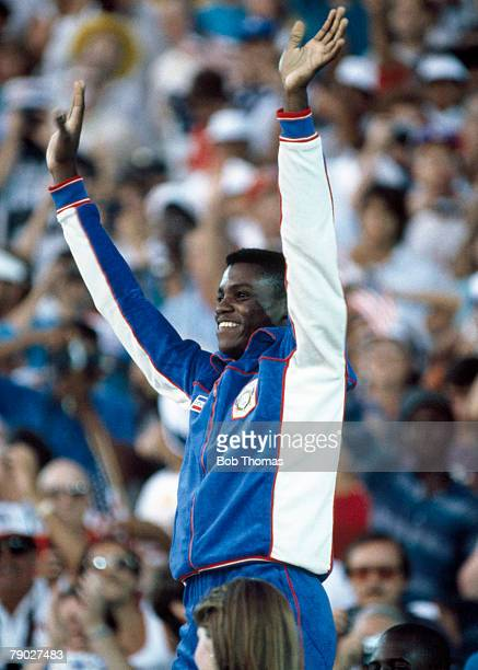 American athlete Carl Lewis celebrates on the medal winners podium before being awarded the gold medal after winning the Men's 100 metres event with...