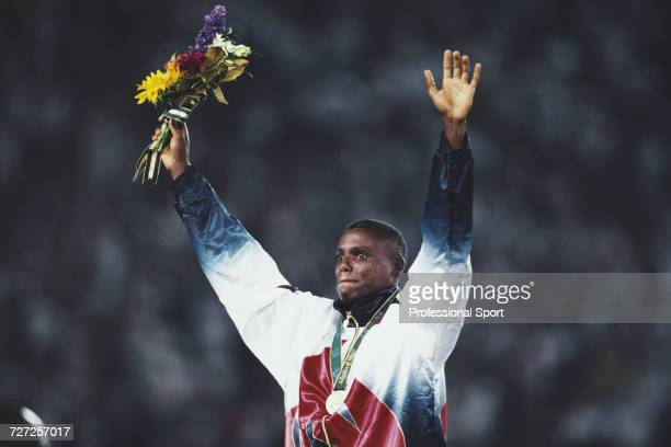 American athlete Carl Lewis raises his arms in the air in celebration on the medal podium after finishing in first place to win the gold medal in the...
