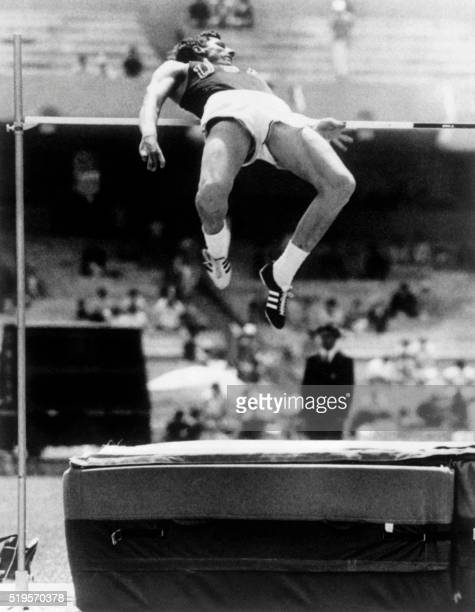 American athlete Dick Fosbury competes in the men's high jump final and wins the gold medal with a brand new style of jumping a dorsal technique on...