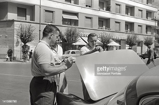 American athlete Harold Connolly checking the boot of a car with the Czechoslovakian athlete Olga Fikotova his wife Rome 1960