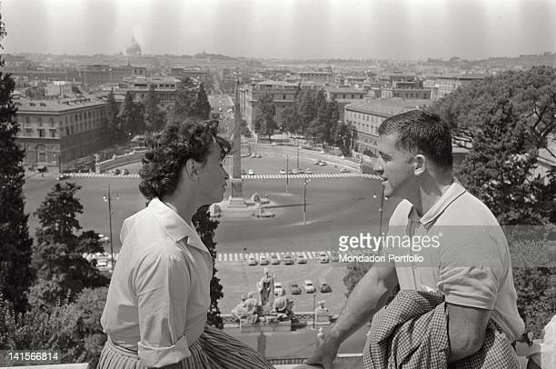 American athlete Harold Connolly sitting on the terrace of the Pincian Hill with the Czechoslovakian athlete Olga Fikotova his wife Behind them...
